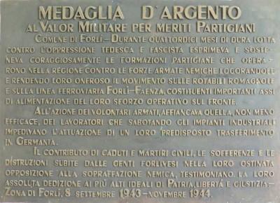 La targa che ricorda la medaglia d'argento per meriti partigiani assegnata al Comune di Forlì. Il bronzo è affisso nello scalone monumentale della casa comunale in piazza Saffi.